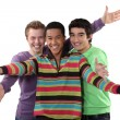 Foto Stock: Three male friends making welcome gesture