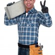 Bricklayer making peace gesture - Stock Photo