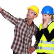 Female architect looking appalled and male builder - Stockfoto