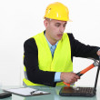 Builder smashing laptop screen with hammer — Stock Photo #11858310