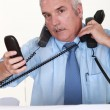 Overwhelmed man answering ringing telephones — Foto de Stock