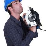 A handyman inspecting his circular saw. — Stock Photo #11858810