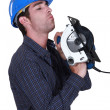 Stock Photo: Handyminspecting his circular saw.
