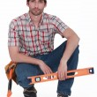 Handyman kneeling with spirit-level - Stockfoto