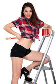 Sexy woman on a ladder painting — Stock Photo