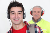 Student wearing headphones in front of a worker wearing ear defenders — Stock Photo