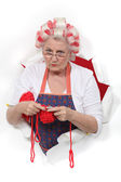 Granny with her hair in rollers and knitting — Stock Photo