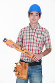 Tradesman holding a spirit level — Stock Photo