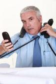 Overwhelmed man answering ringing telephones — Stock Photo