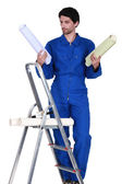 Man stood on step-ladder choosing which color wallpaper to use — Stock Photo