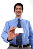 Businessman with toothy smile showing business card — Stock Photo