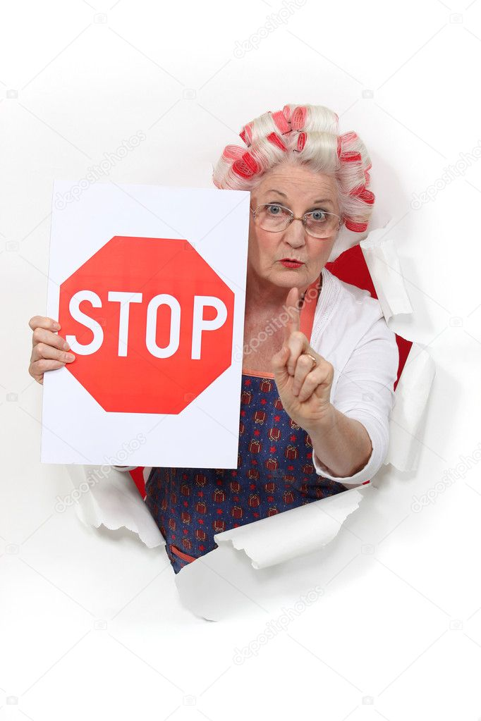 Granny holding a stop sign and with her hair in rollers — Stock Photo #11856256