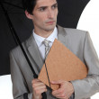 Man with umbrella and folder under his arm - Stock Photo