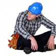 Construction worker sitting cross-legged - Stock Photo