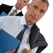 Portrait of a businessman with his assistant trailing behind him — Stock Photo #11868976
