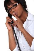 Mulher no telefone fazendo um sinal para o silêncio — Foto Stock
