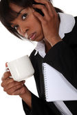 An African American businesswoman on the phone drinking a coffee. — Stock Photo