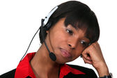 Bored woman wearing a headset — Stockfoto