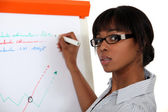 Young woman writing on a paperboard — Stock Photo