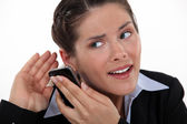 Young businesswoman straining her ears with cell phone — Stock Photo