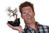 Smoke faced man holding a burnt bonsai — Stock Photo