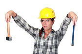 Apprehensive tradeswoman holding a hammer and chisel — Stock Photo