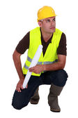 Engineer in a reflective vest with plans — Stock Photo