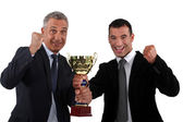 Businessmen holding a golden cup — Stock Photo