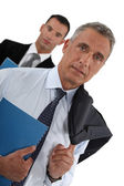 Portrait of a businessman with his assistant trailing behind him — Stock Photo