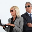 Shady mature business couple with a laptop — Stock Photo #11871317