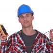 A wide-eyed tradesman holding a multimeter — Stock Photo #11876009