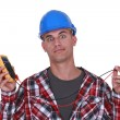 A wide-eyed tradesman holding a multimeter - Stock Photo