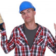 Construction worker holding up a sander — Stock Photo