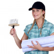 Woman putting up wallpaper - Stock Photo