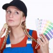 Blonde painter looking inspired holding color chart and brush — Stock Photo #11878139