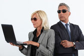 Shady mature business couple with a laptop — Stock Photo