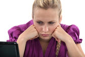 Employee pouting in front of her computer — Stock Photo