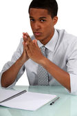 Uninspired young man sitting in front of an empty notebook — Stock Photo