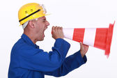 Tradesman screaming into a pylon — Stock Photo