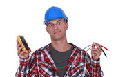 A wide-eyed tradesman holding a multimeter — Stock Photo