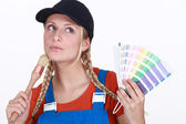 Blonde painter looking inspired holding color chart and brush — Stock Photo