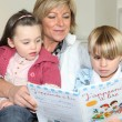 Stock Photo: Mother reading to son and daughter