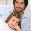 Father and daughter relaxing on a sofa — Stock Photo