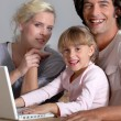 Parents initiating little girl to computer — Stock Photo