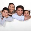 Young family with a board left blank for your image — Stock Photo