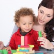 Young mother and little son playing with construction set — Stock Photo