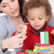 Woman and toddler playing with wooden construction game — Stock Photo