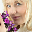 Blonde woman with a sprig of purple wild flowers - Stock Photo