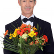 Senior gentleman holding bouquet — Stock Photo