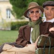 Elegant couple sitting on a park bench — Stock Photo